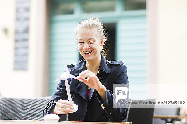 Portrait of laughing blond woman looking at model of wind turbine