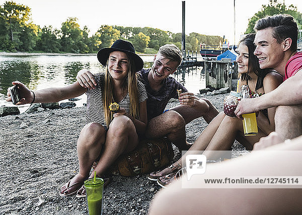 Group of friends sitting together having a barbecue and taking a selfie at the riverside