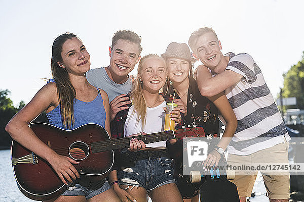 Portrait of group of happy friends with guitar at the riverside
