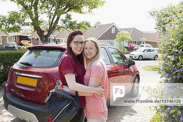 Portrait affectionate lesbian couple hugging in driveway