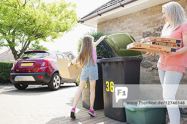 Mother and daughter recycling cardboard in driveway