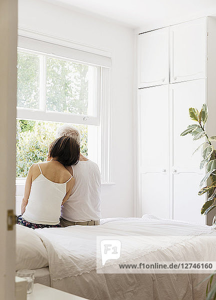 Serene senior couple sitting on bed and looking out window