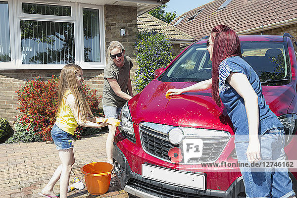 Lesbian couple and daughter washing car in sunny driveway