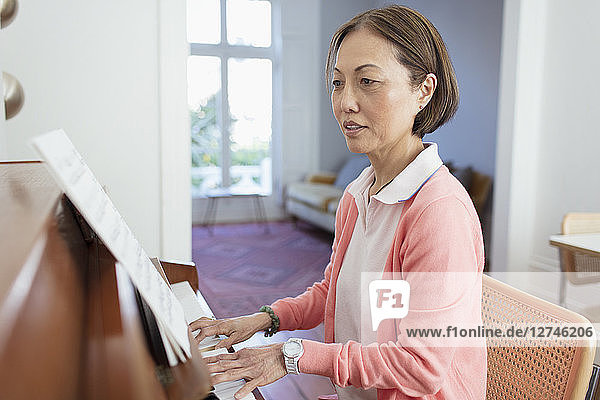 Active senior woman playing piano