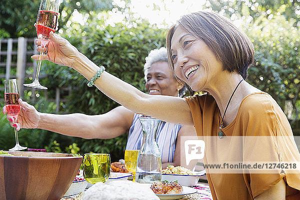 Happy active senior women toasting rose wine at garden party