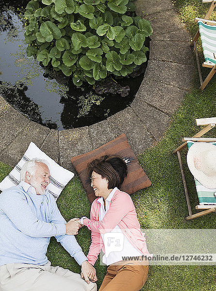 Affectionate senior couple laying by pond in garden