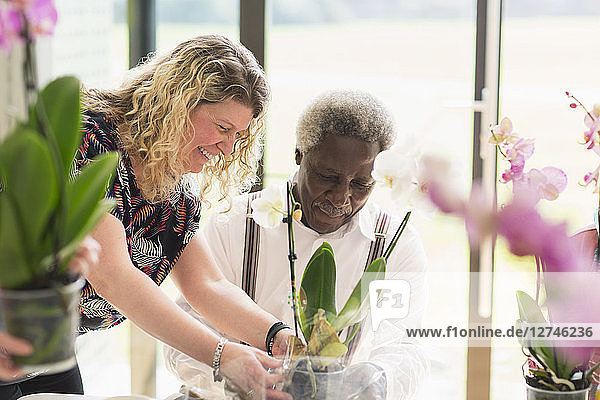 Female instructor helping active senior man in flower arranging class
