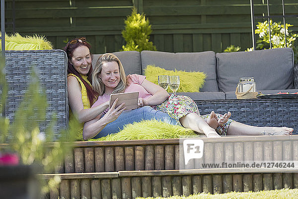 Affectionate lesbian couple using digital tablet  relaxing on patio