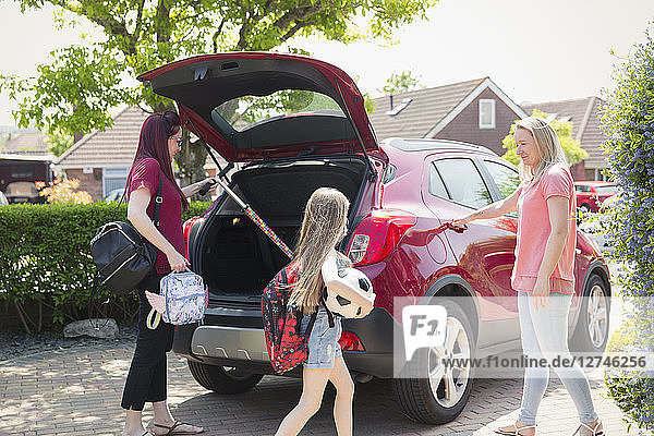 Lesbian couple and daughter loading car for school in sunny driveway