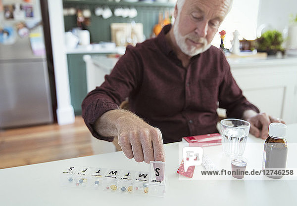 Senior man organizing pill box at kitchen table