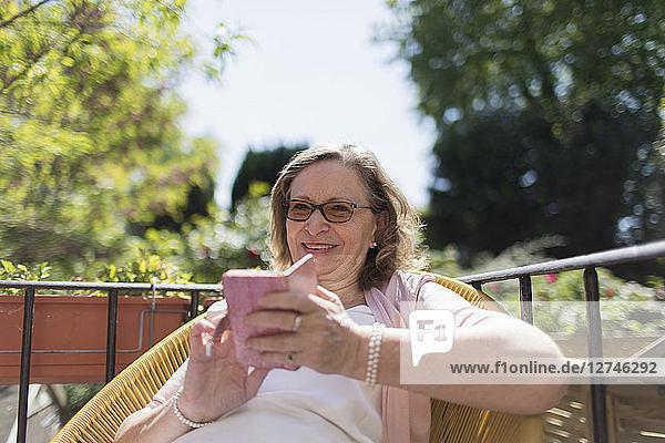 Happy senior woman using smart phone on sunny patio
