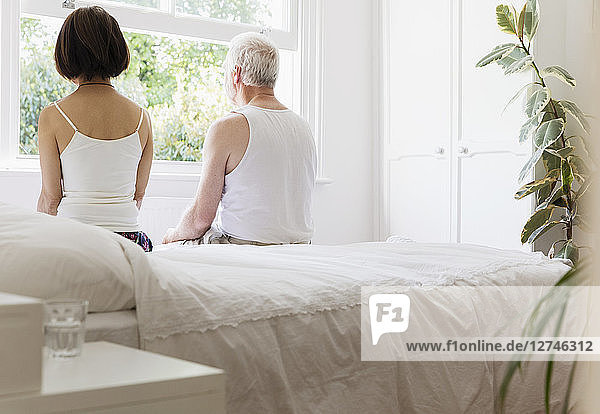 Thoughtful senior couple sitting on bed looking out window
