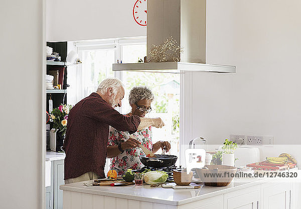 Active senior couple cooking in kitchen