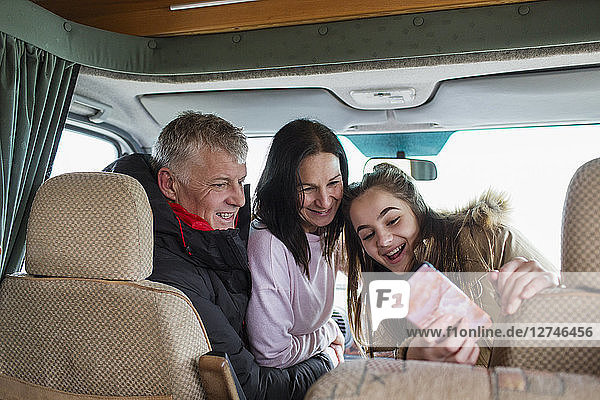 Happy family with smart phone taking selfie in motor home