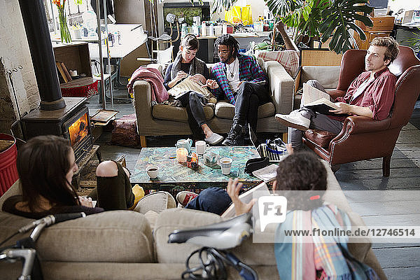 College student roommates studying and hanging out in apartment living room