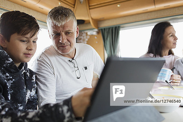 Father and son using digital tablet in motor home