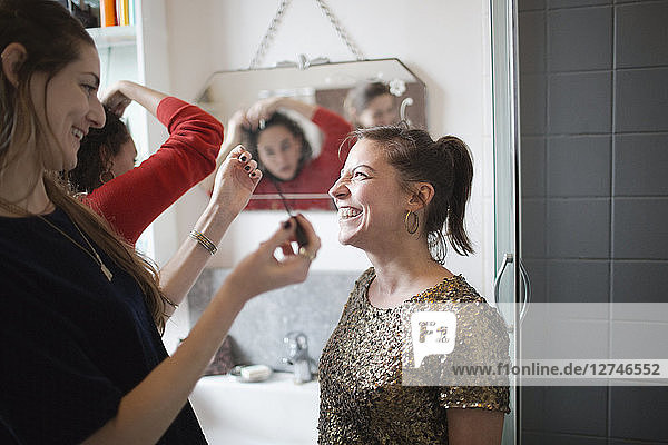 Young women friends getting ready  putting on makeup in bathroom