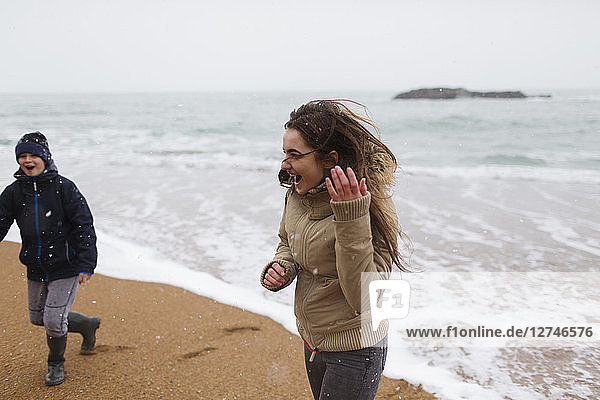 Playful teenage girl on snowy winter beach