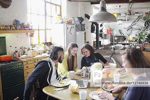 Young college student roommate friends studying at breakfast table in apartment