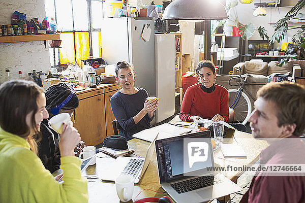 Young college student friends studying at kitchen table in apartment