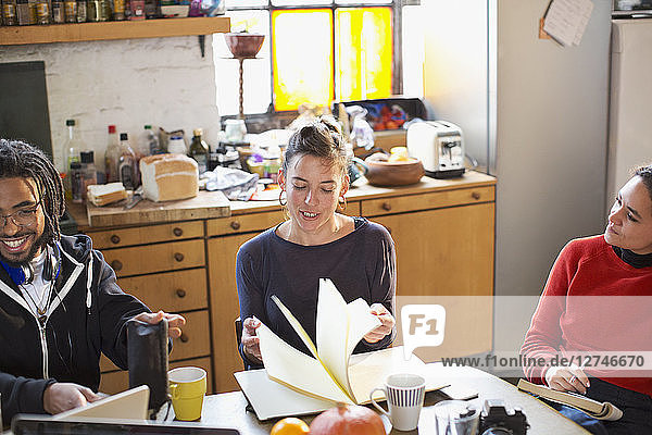 Young college student roommates studying at kitchen table in apartment
