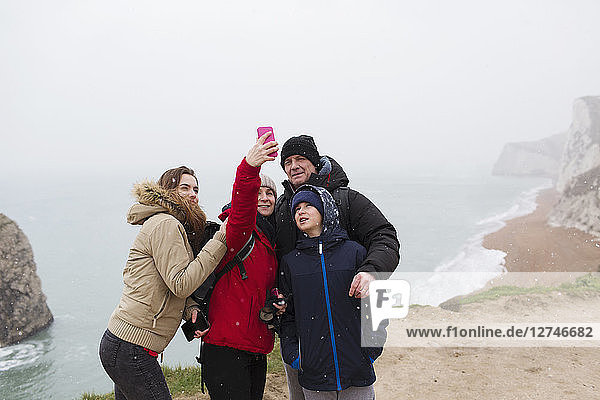 Family with camera phone taking selfie on cliff overlooking ocean