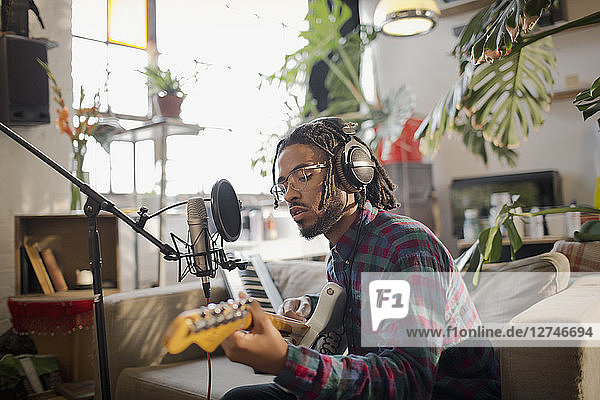Young male musician recording music  playing guitar at microphone in apartment