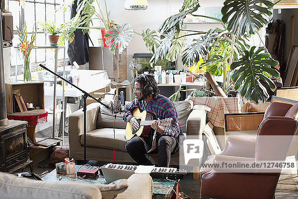 Young male musician recording music  playing guitar and singing into microphone in apartment