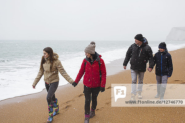 Family in warm clothing walking on snowy winter beach