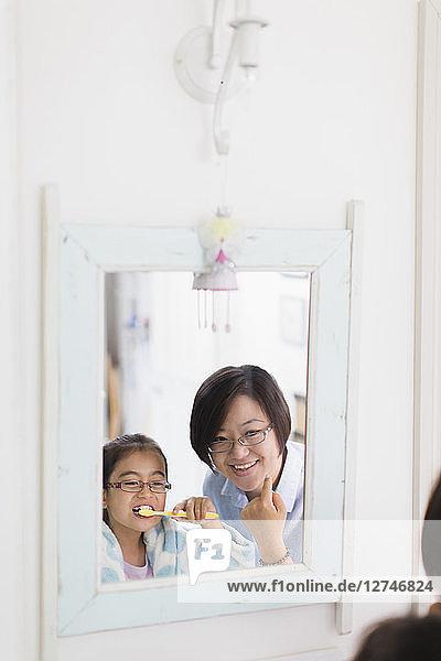 Mother watching daughter brushing teeth in bathroom mirror