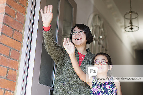 Mother and daughter waving at front door