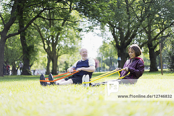 Active senior couple exercising  using resistance bands in park