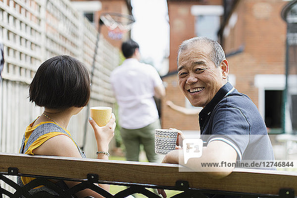 Portrait happy senior man drinking tea with family in back yard