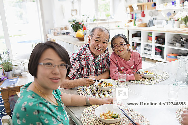 Portrait happy multi-generation family eating noodles with chopsticks at table