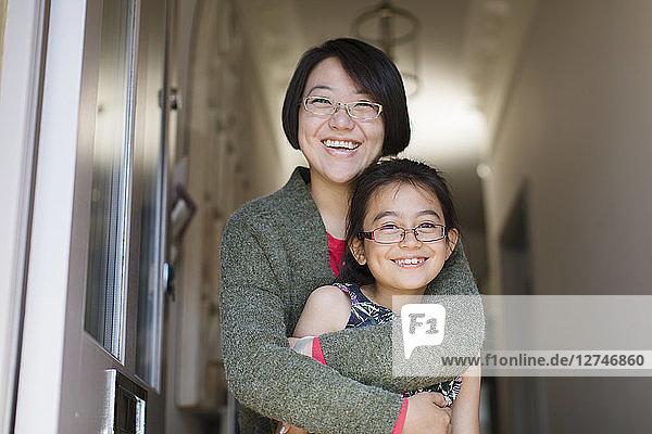 Portrait happy  affectionate mother and daughter hugging in doorway
