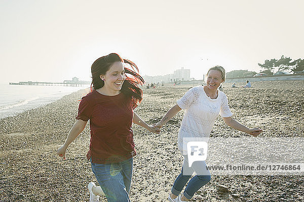 Playful  affectionate lesbian couple holding hands and running on sunny beach