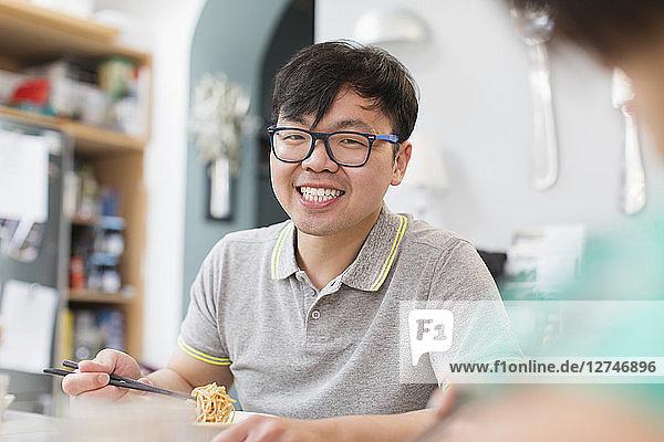 Portrait confident  smiling man eating noodles