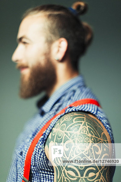Close up hipster man with shoulder tattoo and beard