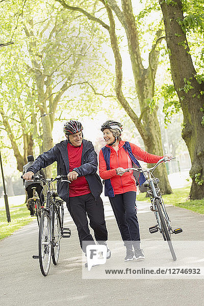 Active senior couple walking bicycles in park