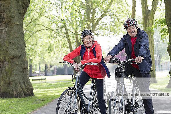 Portrait smiling  confident active senior couple riding bikes in park