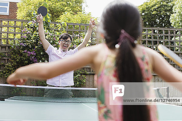 Exuberant father and daughter playing table tennis