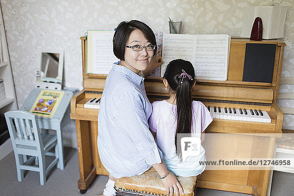 Portrait smiling mother sitting with daughter playing piano