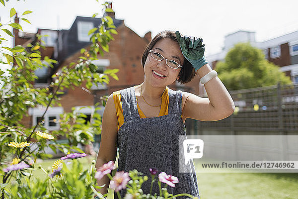 Portrait smiling woman gardening in sunny yard