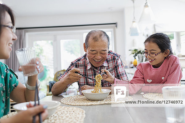 Grandfather and granddaughter sharing noodles at table