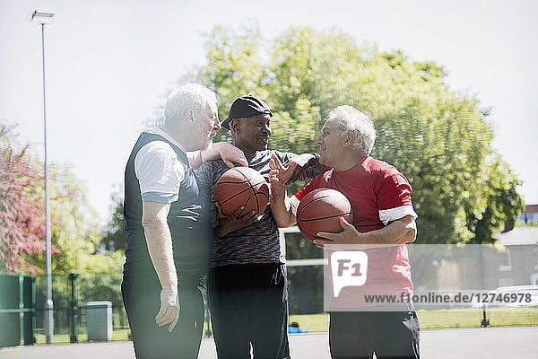 Active senior men friends playing basketball in sunny park