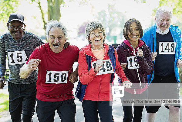 Portrait enthusiastic active senior friends running sports race