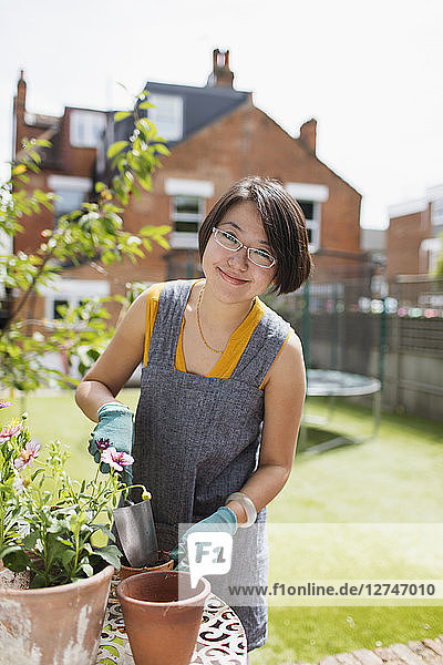 Portrait smiling woman gardening  potting flowers in sunny yard