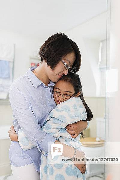 Affectionate mother and daughter hugging in bathroom