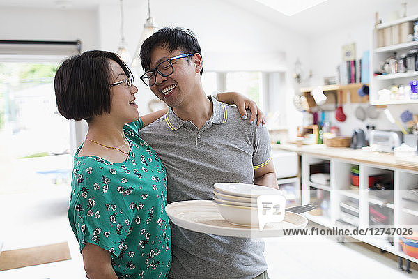 Affectionate couple hugging  doing dishes in kitchen