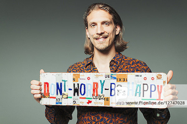 Portrait smiling young man holding Dont Worry Be Happy license plates Portrait smiling young man holding Dont Worry Be Happy license plates